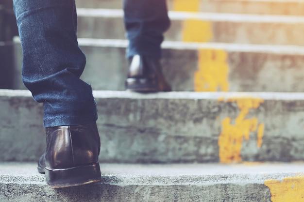 現代の都市の階段を上って歩いてクローズアップの足で働く現代のビジネスマン。急いでオフィスで働くためにラッシュアワーに。仕事の最初の朝の間。階段。