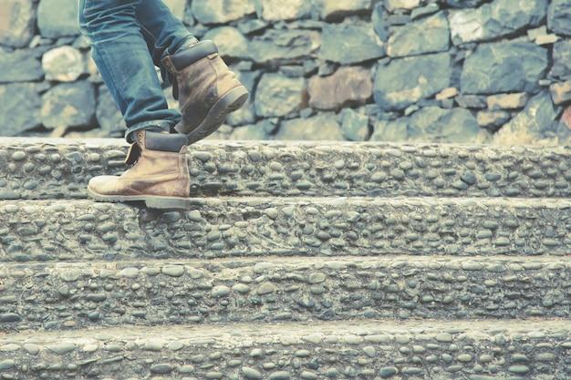 現代の都市の階段を上って歩いてクローズアップの足で働く現代のビジネスマン。急いでオフィスで働くためにラッシュアワーに。