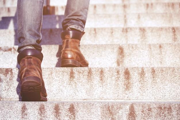 現代のビジネスマンは、近代的な都市の階段を上って歩いてクローズアップの足で働いています。