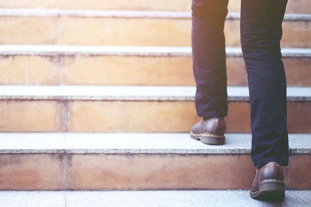 Modern businessman working  closeup legs walking up the stairs in modern city.
