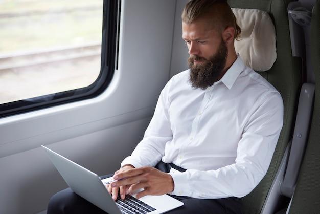 Uomo d'affari moderno che lavora in treno