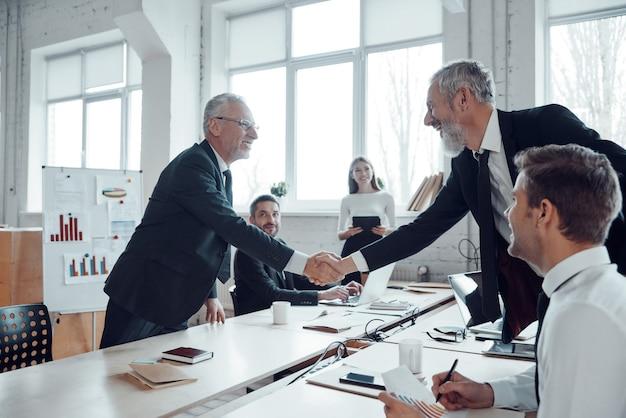 Современные бизнесмены пожимают друг другу руки, работая вместе со своей командой в офисе