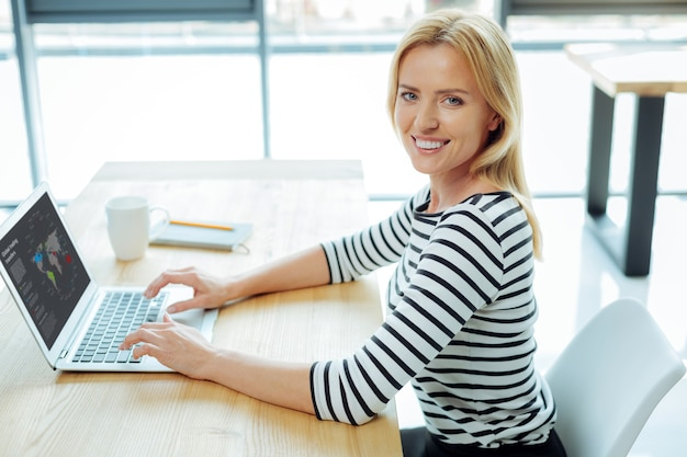 現代の実業家。ノートパソコンで作業しながら笑顔で世界地図を見ている陽気な前向きなインテリジェントな女性