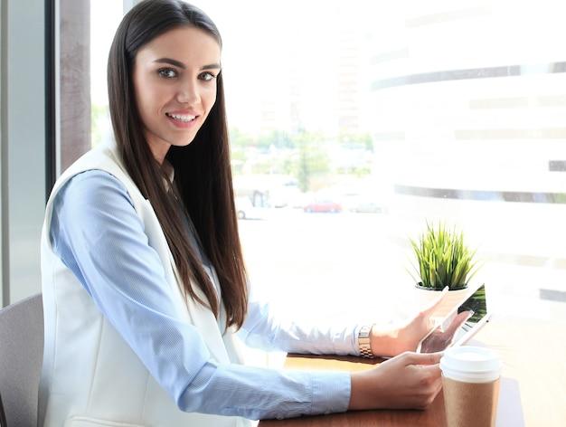 Современная деловая женщина пьет кофе в офисном кафе во время обеда и с помощью планшета