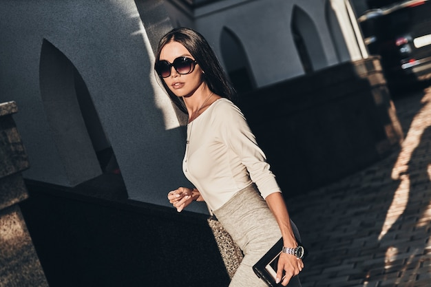 Modern businesswoman on the go. attractive young woman carrying her smart phone and wallet while walking outdoors