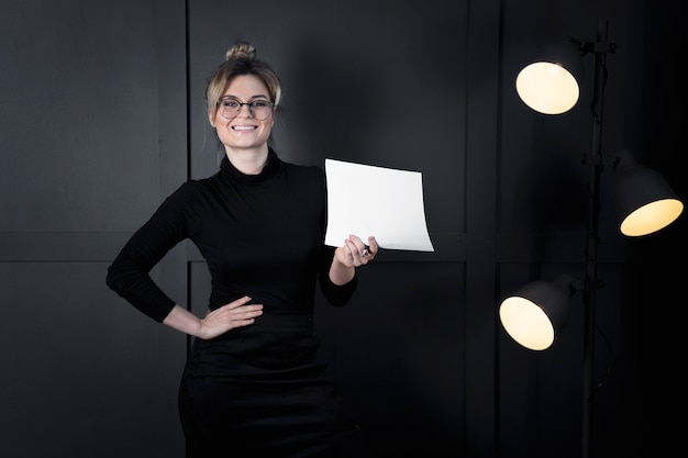 Modern businesswoman holding papers at the office