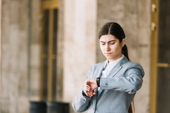 Modern businesswoman looking at watch outdoors