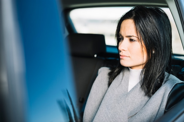 Modern businesswoman sitting in car
