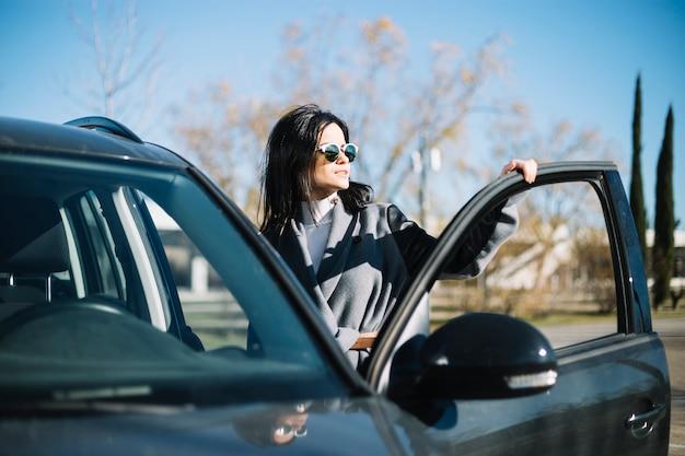 Modern businesswoman standing next to car