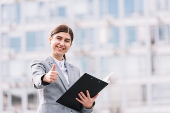 Modern businesswoman with clipboard outdoors