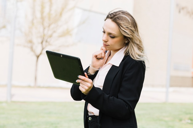 Modern businesswoman with laptop outdoors