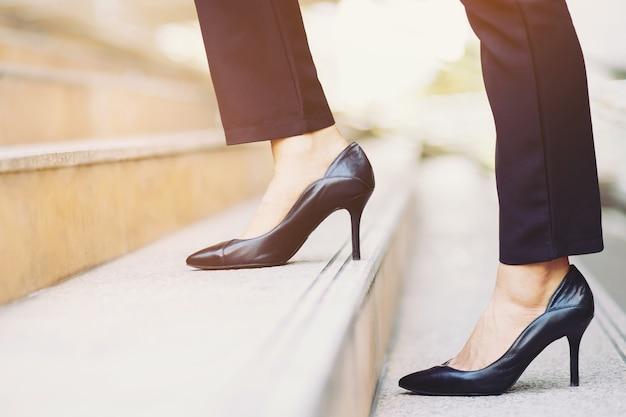 현대 사업가 작업 여자 사무실에서 서둘러 일하기 위해 러시아워에 현대 도시의 계단을 걸어 다리를 닫습니다