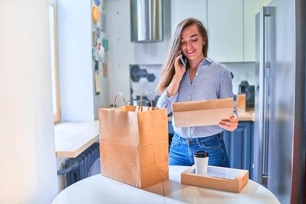 Современный занятый случайный милый взрослый счастливый улыбающийся клиент молодой женщины получил картонные пакеты с едой и напитками на вынос дома. концепция службы быстрой доставки