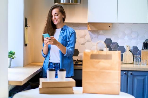 Современная занятая милая улыбающаяся радостная счастливая случайная женщина-миллениал получила картонные пакеты и бумажные стаканчики с едой и напитками на вынос. концепция быстрой доставки на дом