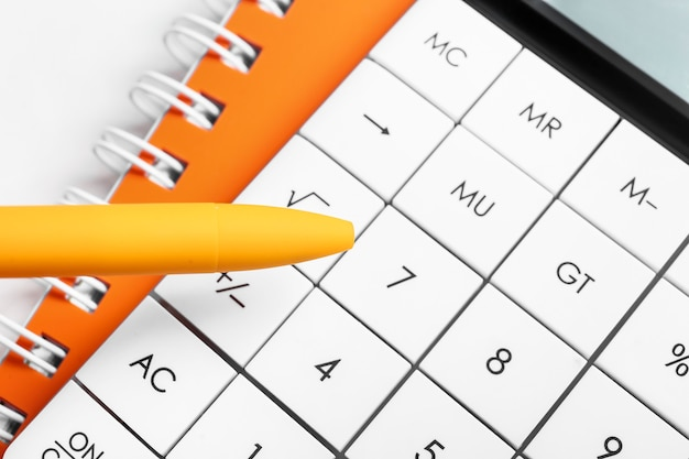 Современный калькулятор и ручка, крупным планом