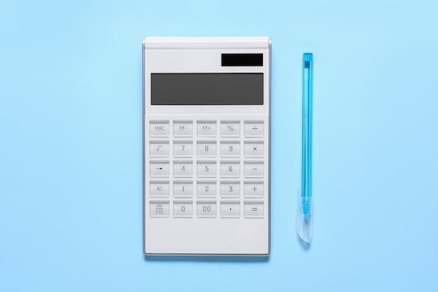 Современный калькулятор и ручка на цветной поверхности