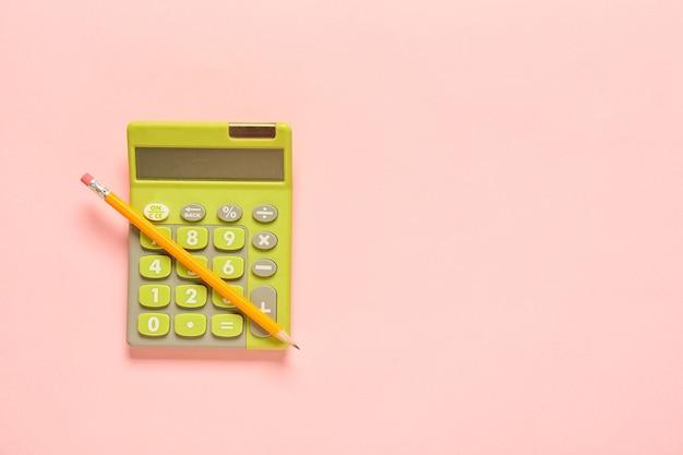 Современный калькулятор и карандаш на цветной поверхности