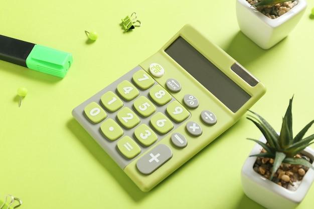 Современный калькулятор и канцелярские товары на цветной поверхности