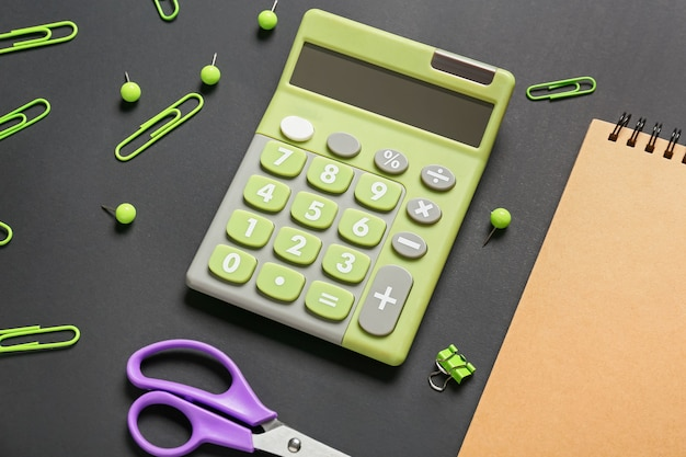 Современный калькулятор и канцелярские товары на темной поверхности