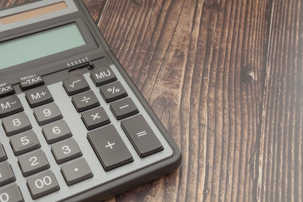 Modern calculator, business and finance accounting concept wooden background.