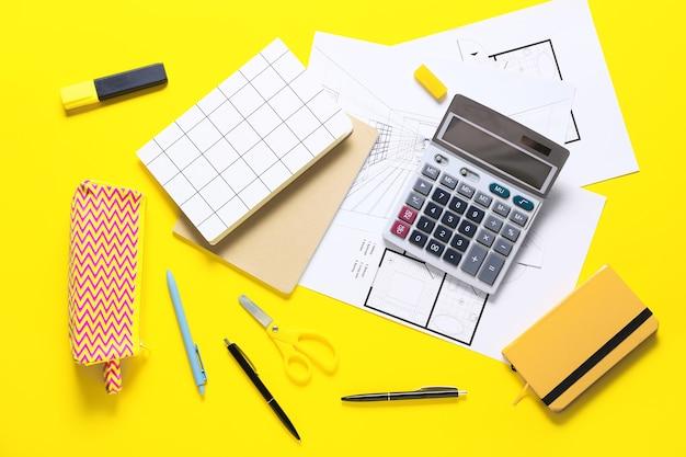 Современный калькулятор с планами дома и канцелярскими принадлежностями на цветной поверхности