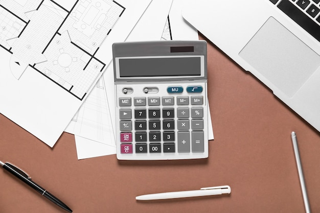 Modern calculator with house plans and laptop on color surface