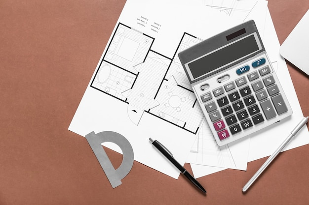 Modern calculator with house plans and stationery on color surface