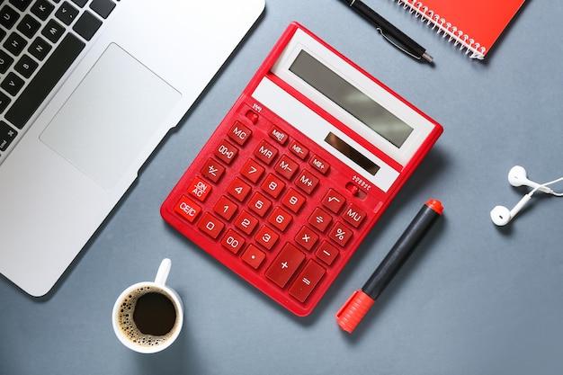 灰色の表面にラップトップと文房具を備えた最新の電卓