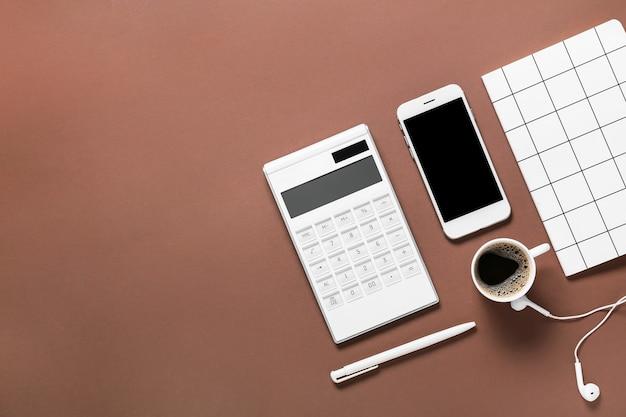 携帯電話、一杯のコーヒー、色の表面に文房具を備えた最新の電卓