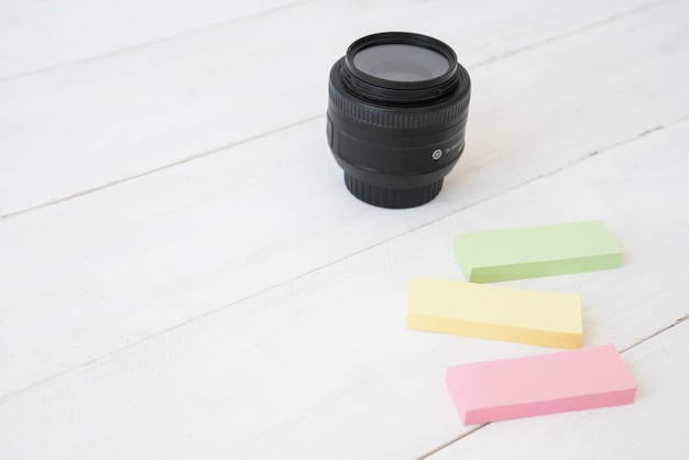 Modern camera lens with colorful sticky notes on wooden desk