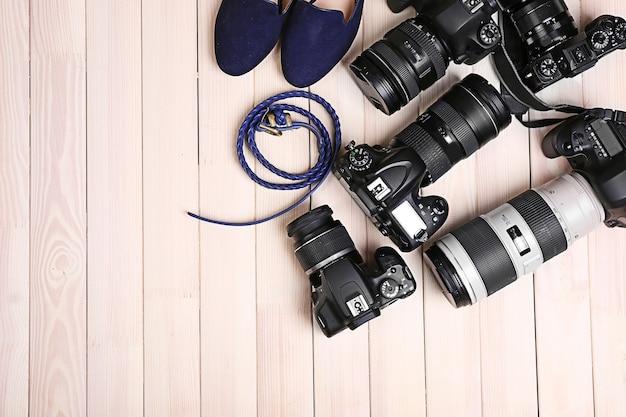 Современные камеры с женскими туфлями и поясом на деревянном столе, вид сверху