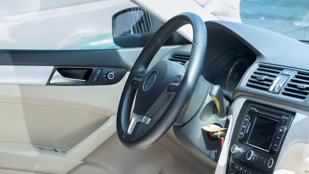 Modern car interior, driver's seat. white black leather and metal.