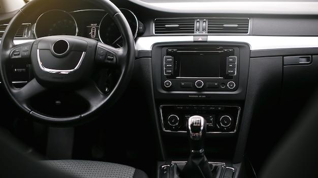 モダンな車のインテリア。ステアリングホイール、ギアシフトレバー、マルチメディアシステム、運転席、ダッシュボード。