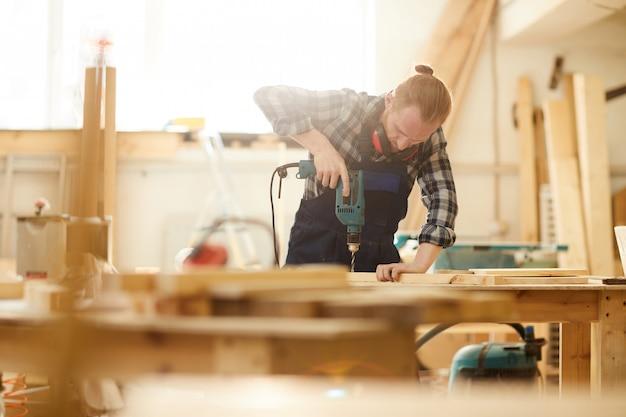 Modern carpenter drilling wood