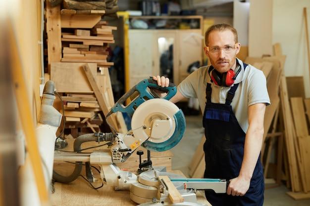 Modern carpenter posing in workshop