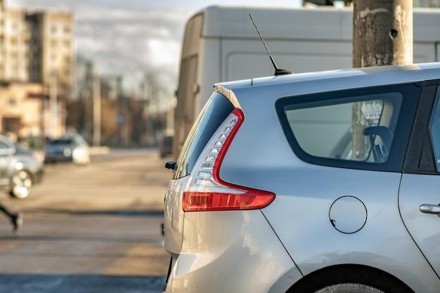 Современные автомобили, припаркованные на стороне улицы города в солнечный день.