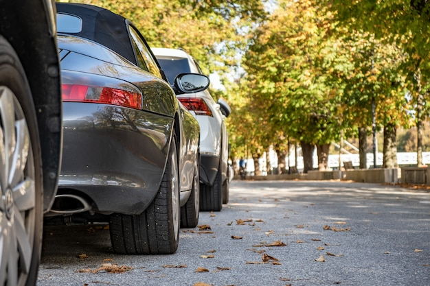 Современные автомобили, припаркованные на улице города в жилом районе.