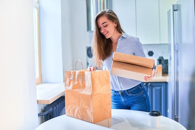 Современный случайный милый взрослый счастливый улыбающийся молодой клиент из тысячелетия получил дома картонные пакеты с едой и напитками на вынос. концепция службы быстрой доставки