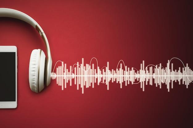 오디오 트랙이 있는 빨간색 그라데이션 배경의 현대적인 셀 흰색 전화 및 헤드폰 템플릿입니다. 음악 개념입니다.