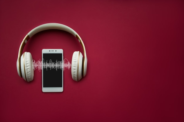Modern cell white phone and headphones template on red gradient background with audio track. music concept.