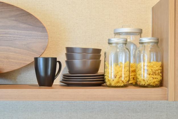 Modern ceramic kitchenware and utensils on pantry shelf