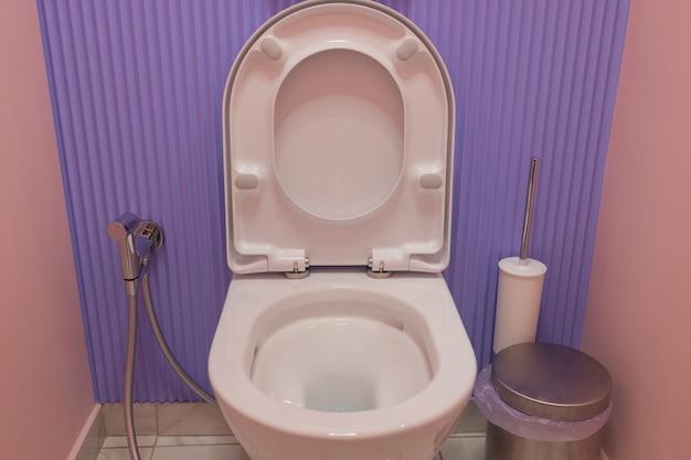 トイレの色の壁の近くにあるモダンなセラミック便器。