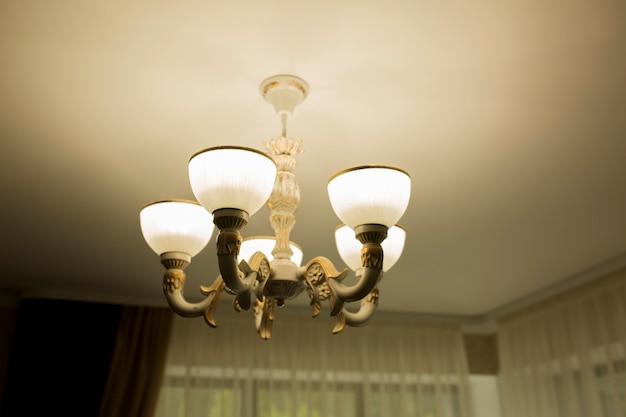 部屋の白い天井にモダンなシャンデリア。クローズアップショット