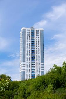 하늘을 배경으로 언덕 꼭대기에 있는 현대적인 저렴한 다층 아파트