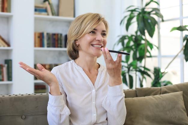 現代の陽気な中年女性が自宅のソファに座って、仮想デジタル音声アシスタントを使用して、スピーカーでスマートフォンの会話を保持します。