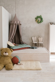 Modern childrens room a tent bed on the podium soft toys high chairs in the form of bunnies