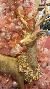 빈티지 질감 오버레이가 있는 눈 속에서 전구와 은색 순록이 있는 현대적인 크리스마스 트리.