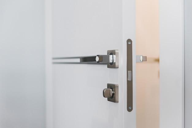 Modern chrome door handle and lock on white wooden door.
