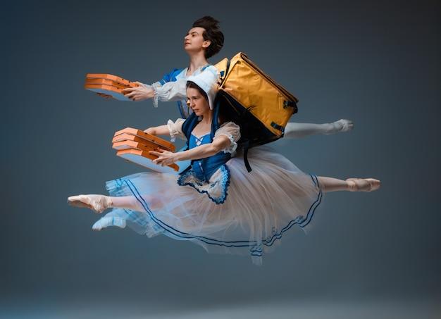 피자를 배달하는 현대 신데렐라와 왕자님. 스튜디오 배경에 젊고 우아한 발레 댄서입니다. 예술, 모션, 액션, 유연성, 영감 개념. 빠른 주문 배송.