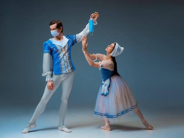 현대 신데렐라는 슬리퍼를 신지 않고 보호용 안면 마스크를 착용합니다. 스튜디오 배경에서 공연하는 동안 젊고 우아한 발레 댄서. 예술, 모션, 액션, 유연성, 영감 개념.